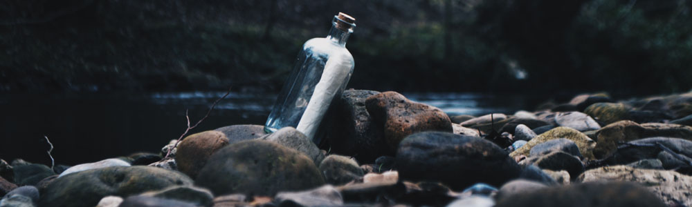 Message in a bottle sitting on stones by a river