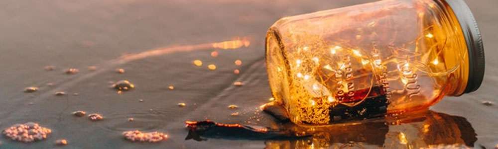 Image of jar on sandy beach with small white string lights